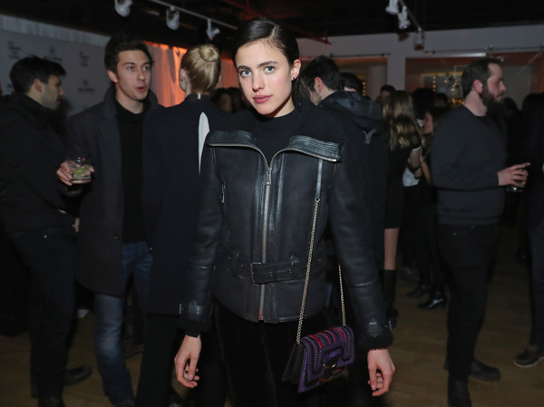 Margaret Qualley splashed on some color with a purple and red suede bag.