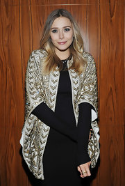 Elizabeth Olsen added elegant glitz to her long-sleeved dress with a gilded evening coat.