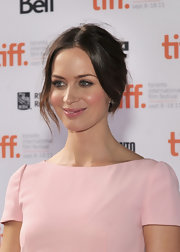 Emily Blunt's loose updo can be recreated by making a center part, sectioning out a few face-framing strands and pulling the rest back into a loose pony tail. Twist the tail, wrap ends back into hair elastic and secure with a few bobby pins.