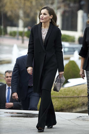 Queen Letizia styled her outfit with a multicolored woven clutch.
