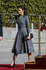 Queen Letizia of Spain teamed a studded leather clutch by Hugo Boss with a gray wrap dress and black pumps for her flight to Morocco.