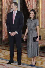 Queen Letizia pulled her look together with a textured black leather clutch, also by Magrit.