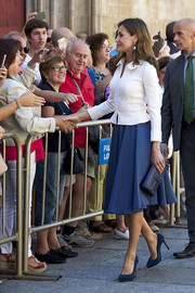 Queen Letizia of Spain teamed a rhinestone-embellished leather clutch with a blue skirt and a white jacket for the opening of the Scholar University College year.