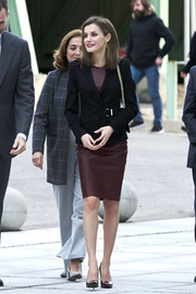 Queen Letizia visited CNIC in Madrid wearing a burgundy leather sheath dress by Hugo Boss.
