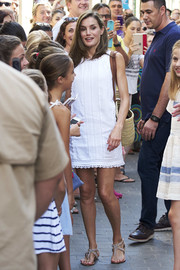 Queen Letizia of Spain teamed a pair of rhinestone-embellished thong sandals by Uterque white a white shift dress for a visit to the Can Prunera Museum in Palma de Mallorca.
