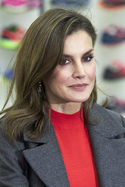Queen Letizia of Spain wore her hair down to her shoulders in a gently wavy style while visiting the Joma Sport factory.
