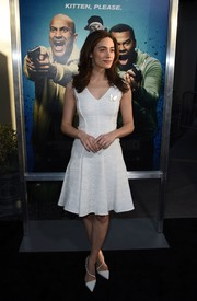 White Louboutin pumps with diagonal straps completed Emmy Rossum's ladylike look.