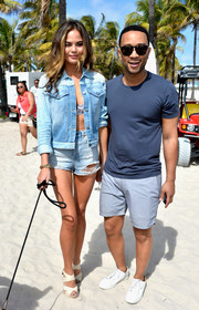 Chrissy Teigen hit the beach for the SI Swimsuit Beach Volleyball Tournament wearing a faded denim jacket.