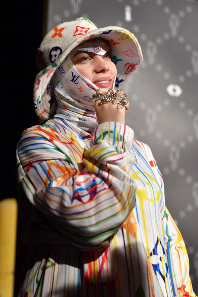 Billie Eilish accessorized with a colorful LV logo-print bucket hat by Tsuwoop at the Billie Eilish Experience event.