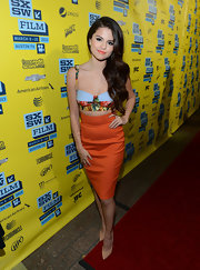 Selena Gomez opted for the tropical look with this orange pencil skirt and bustier top.