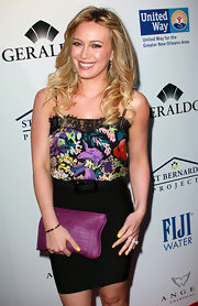Hilary Duff highlighted the purple floral pattern of her blouse with a sweet bow imprinted leather clutch.