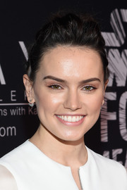 Daisy Ridley pulled back her hair for a messy updo that showed off her face.