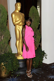 Viola accessorized her bright pink cocktail dress with taupe strappy sandals.