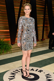 Jennifer Lawrence went for a provocative party look during the Vanity Fair Oscar party in a mirrored Tom Ford dress with see-through panels down both sides.
