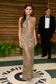 Selena Gomez looked absolutely divine at the Vanity Fair Oscar party in a beaded gold Emilio Pucci halter gown with a navel-grazing keyhole neckline.