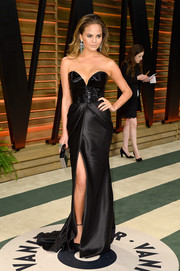 Chrissy Teigen smoldered at the Vanity Fair Oscar party in a black Naeem Khan strapless gown with a low sweetheart neckline and a thigh-baring slit.