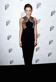 Riley Keough cut a striking figure in her black column gown with fishnet details.
