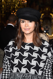 Miroslava Duma accessorized with a black captain's cap when she attended the Stella McCartney fashion show.