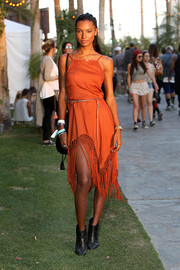 Jasmine Tookes was hippie-chic in a red-ochre Urban Outfitters dress with a fringed wave hem during Coachella.
