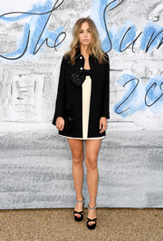 Suki Waterhouse layered a black wool coat over a bowed white mini dress, both by Miu Miu, for the 2019 Serpentine Gallery Summer Party.