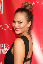 A pair of gemstone chandelier earrings by Lorraine Schwartz provided a glamorous finish to Chrissy Teigen's look.