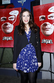 Liv Tyler layered a cropped asymmetrical blazer over her flirty floral dress.