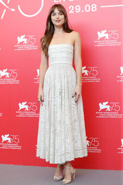 Dakota Johnson was all about summertime charm in a strapless white lace dress by Dior at the Venice Film Festival photocall for 'Suspiria.'