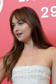 Dakota Johnson wore her long hair loose in a casual straight style with parted bangs at the Venice Film Festival photocall for 'Suspiria.'