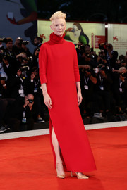 Tilda Swinton styled her gown with gold ankle-strap pumps by Manolo Blahnik.