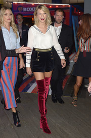 Taylor Swift teamed her blouse with blue velvet shorts, also by Tommy Hilfiger.