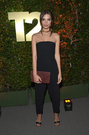 Emily Ratajkowski paired her outfit with a burgundy envelope clutch.