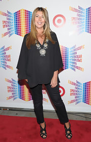 Nina Garcia disguised her baby bump with a loose black blouse featuring an embellished neckline.