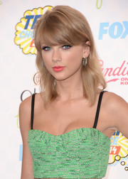 Taylor Swift's pink lipstick contrasted nicely with her green outfit.