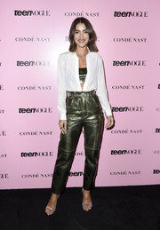 Camila Coelho attended the 2019 Teen Vogue Summit wearing an unbuttoned white shirt with a metallic bandeau top underneath.