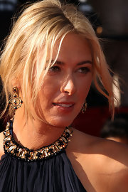 Maria Sharapova perfectly paired her McQueen dress with a pair of decorative yellow gold earrings with black diamonds.