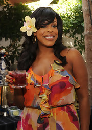 Niecy donned a signature floral hair pin with a colorful ruffled cocktail dress.
