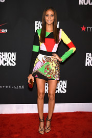 Joan Smalls completed her ultra-modern look with a geometric gold clutch by Lee Savage.