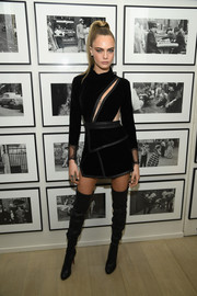 Cara Delevigne amped up the edgy-chic vibe with a pair of black thigh-high boots by Christian Louboutin.