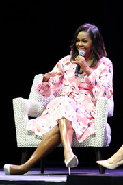 Michelle Obama looked vibrant in a belted pink print dress by Tanya Taylor while attending a live conversation with the Women's Foundation of Colorado.