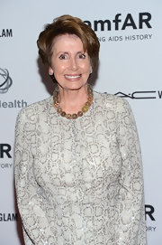 Nancy Pelosi added a subtle glass marble necklace to complement her snakeskin print outfit during the Together to End Aids Event.