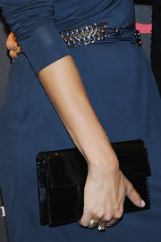 Helena carries a simple but elegant patent leather clutch.