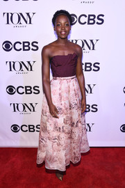 Lupita Nyong'o went for ladylike elegance in an Oscar de la Renta strapless dress with a structured bodice and a printed skirt during the Tony Honors cocktail party.