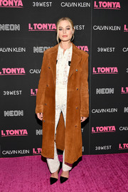 Margot Robbie toughened up her white lace separates with a camel-colored suede coat by Calvin Klein for the New York premiere of 'I, Tonya.'