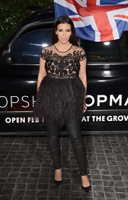 Kim Kardashian showed off her glamorous style with a black mesh and silk top with a feather peplum.