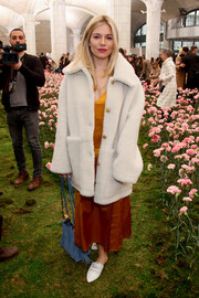 Sienna Miller kept her feet comfy in a pair of white slippers, also by Tory Burch.