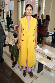 Caroline Issa did some color blocking for the Tory Burch fashion show, layering a bright yellow coat over a lavender dress.