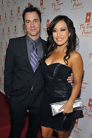 Carrie Ann Inaba added a dose of shine to her gleaming strapless dress with a metallic silver clutch.
