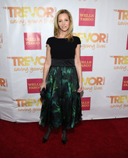 Lisa Kudrow posed on the TrevorLIVE LA red carpet wearing a cocktail dress with a fitted black bodice and a green print skirt.