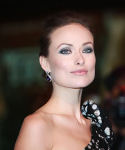 Olivia Wilde paired her elegant updo with diamond drop earrings adorned with a decadent purple stone.