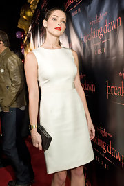 Ashley Greene contrasted her classic white sheath dress with a sleek black hard case clutch.
